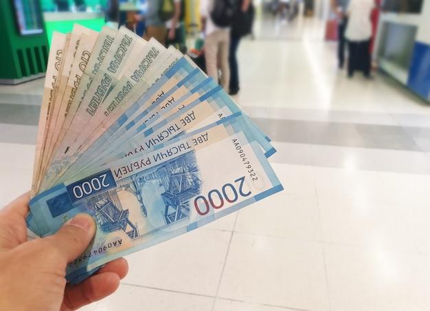 Mão segurando dinheiro liso rublo russo notas, negócios e conceito de finanças.