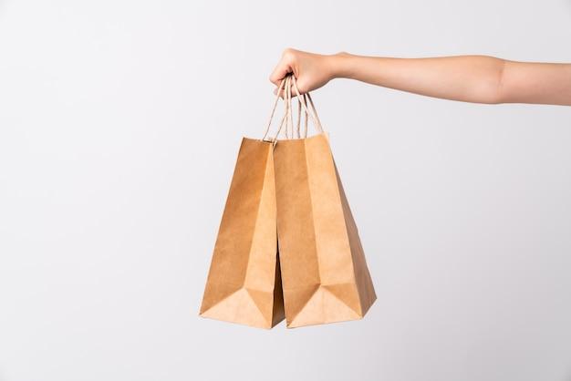 Mão segurando dois sacos de papel artesanal em branco em fundo branco