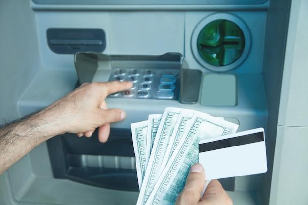 Mão segurando dólares e cartão de crédito retirado do caixa eletrônico.