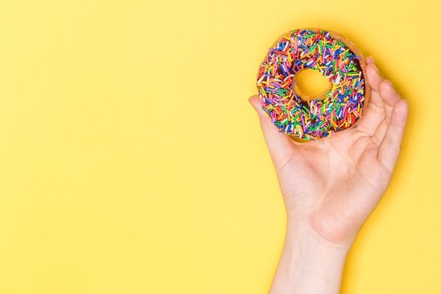 Mão segurando donut de chocolate fosco com granulado, glaceado com açúcar glaceado em fundo amarelo.
