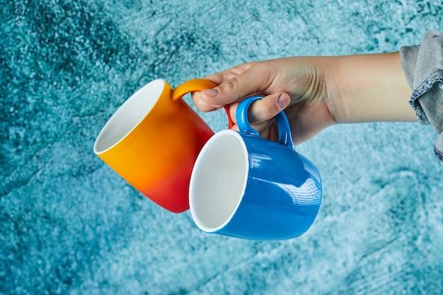 Mão segurando duas canecas sobre fundo azul.