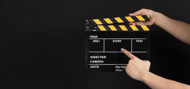 Mão segurando e aponte para claquete amarelo e preto ou filme ardósia uso na produção de vídeo e na indústria do cinema em fundo preto.