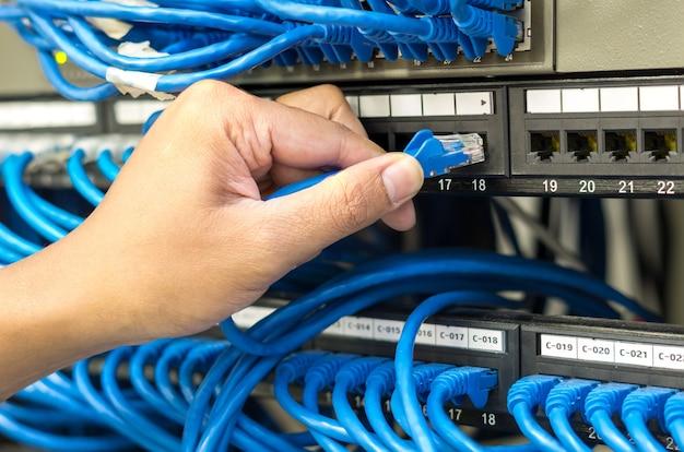 Mão segurando e conectando o cabo de rede conectar ao roteador e switch hub na sala do servidor
