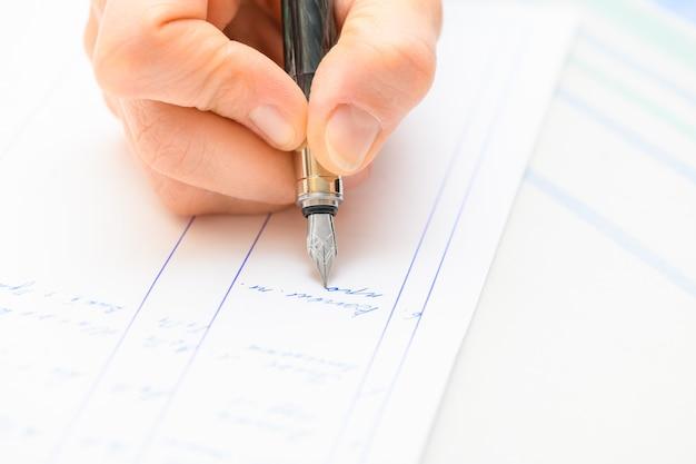 Mão segurando e escrevendo uma nota com uma caneta-tinteiro