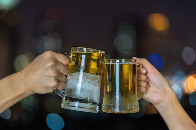 Mão segurando e tinindo com dois caneca de cerveja