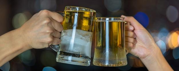Mão segurando e tinindo com duas caneca de cerveja ou óculos sobre a foto desfocada da paisagem urbana