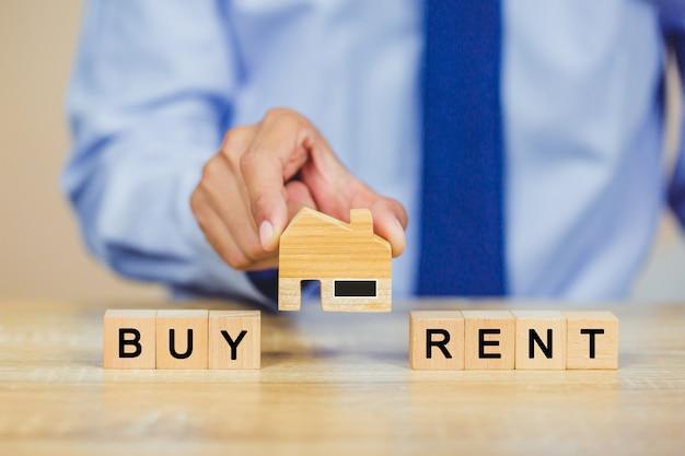 Mão segurando em casa com comprar ou alugar, conceito imobiliário.