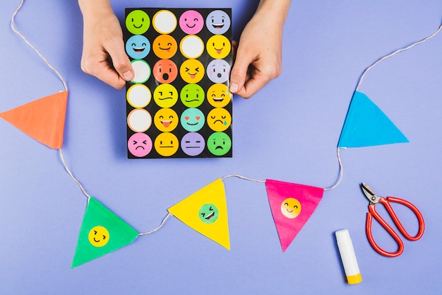 Mão, segurando, emoji, adesivos, jogo, perto, coloridos, bunting, com, scissor, e, cola, vara