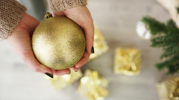 Mão segurando enfeites de bola de ouro no fundo da árvore de natal