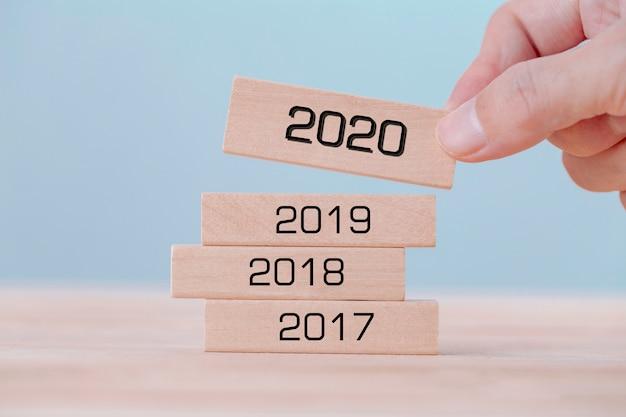 Mão segurando escolhe cubos de blocos de madeira com a palavra 2020