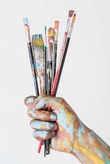 Mão segurando escovas manchadas com tinta