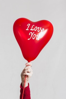 Mão segurando eu te amo balão