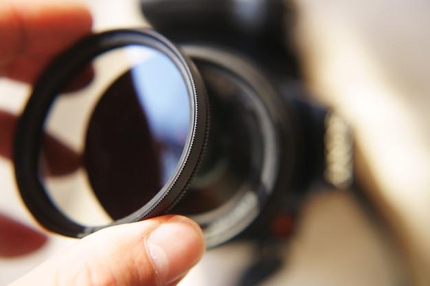 Mão segurando filtro de lente de câmera dslr