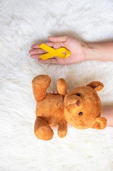 Mão segurando fita amarela e boneca de urso em fundo branco para apoiar a vida de criança e doença. setembro mês de conscientização do câncer infantil e conceito do dia mundial do câncer