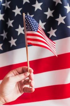 Mão, segurando, flagpole, com, bandeira americana