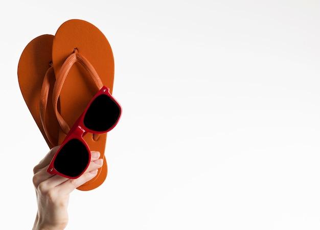 Mão segurando flip-flops com óculos de sol e espaço de cópia
