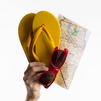 Mão segurando flip-flops com óculos de sol e mapa