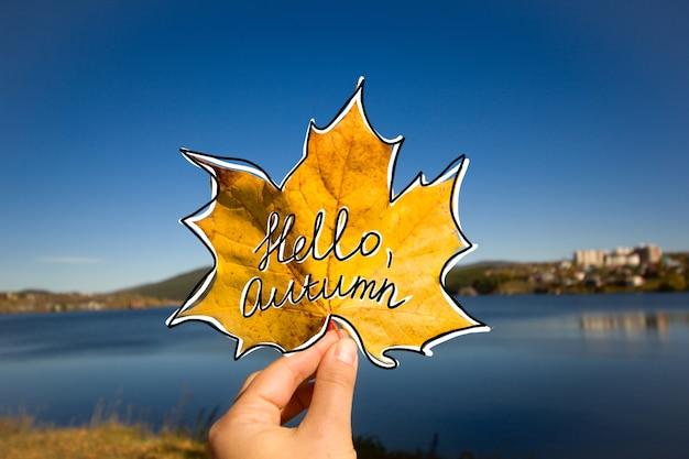 Mão segurando folha amarela de maple outono com texto manuscrito olá outono contra céu azul