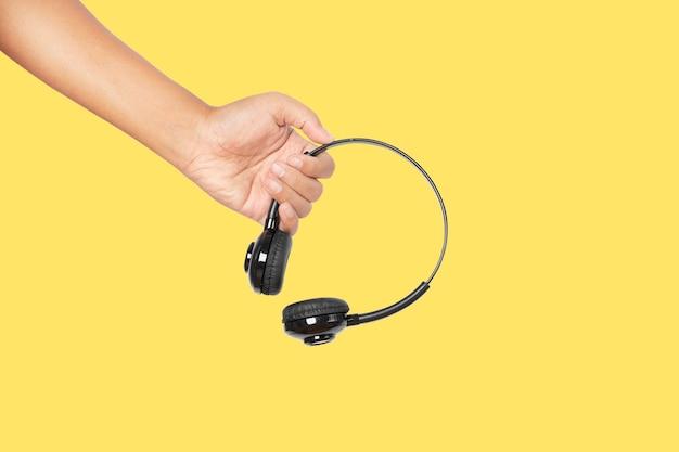 Mão segurando fones de ouvido isolados em fundo amarelo