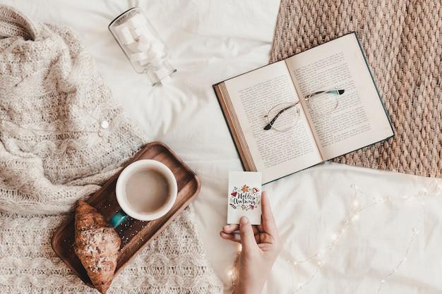 Mão segurando fraque perto de livro, óculos, comida e manta