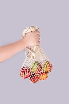 Mão segurando frutas, legumes em um saco de algodão de malha reutilizável, conceito de plástico sem desperdício zero