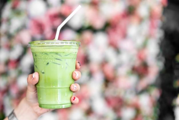 Mão segurando gelado matcha latte xícara de chá verde
