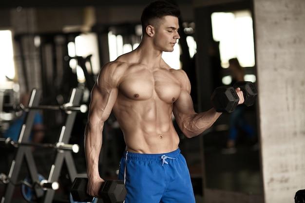 Mão segurando halteres. close up. braço muscular no ginásio.