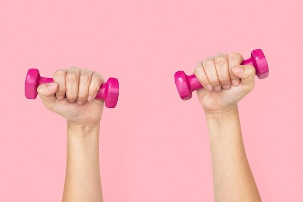 Mão segurando halteres no conceito de saúde e bem-estar
