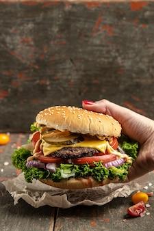 Mão segurando hambúrguer delicioso fresco, conceito de fast food e junk food, banner, menu, local de receita para texto