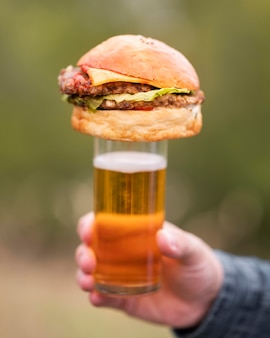 Mão segurando hambúrguer em cima de um copo