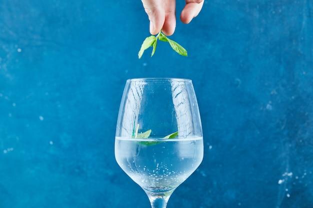 Mão segurando hortelã em cima do suco na superfície azul