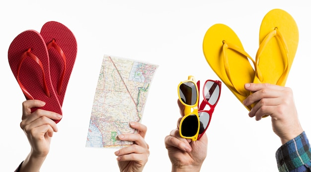 Mão segurando itens de viagem com chinelos e óculos de sol