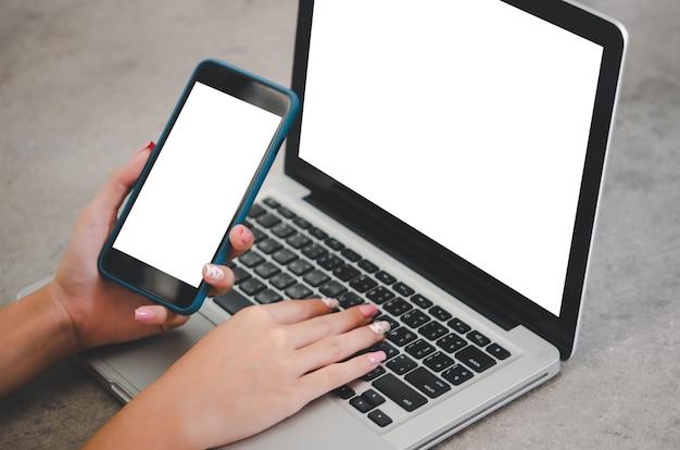 Mão segurando laptop de computador de tela em branco de imagem de maquete de telefone para texto de publicidade na mesa do local de trabalho no escritório.