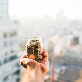 Mão segurando lata com moedas