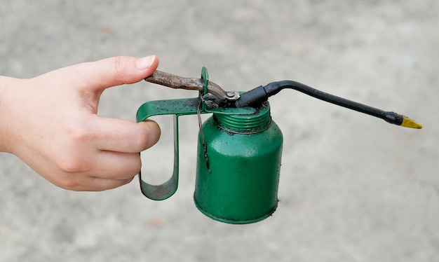 Mão segurando lata de óleo velho e sujo