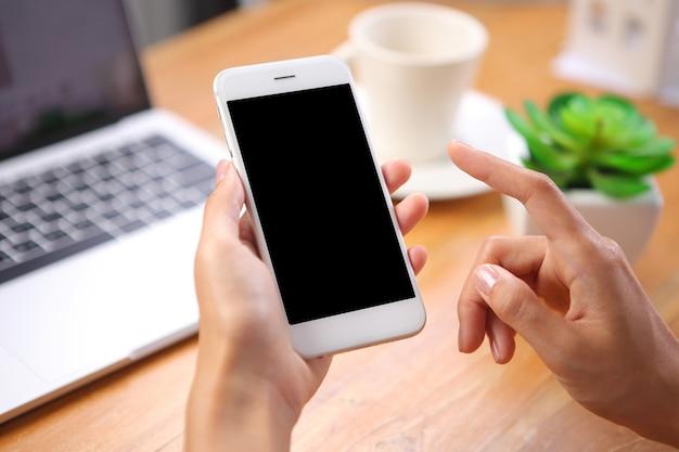 Mão segurando maquete de smartphone com laptop e papelaria de escritório na mesa de madeira