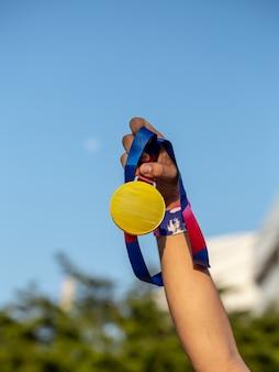 Mão segurando medalha no fundo do céu, vencedor e conceito de sucesso