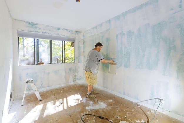 Mão segurando melhorias na casa de ferramentas de gesso. colocando gesso na parede com espátula