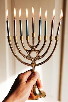 Mão segurando menorah com velas acesas