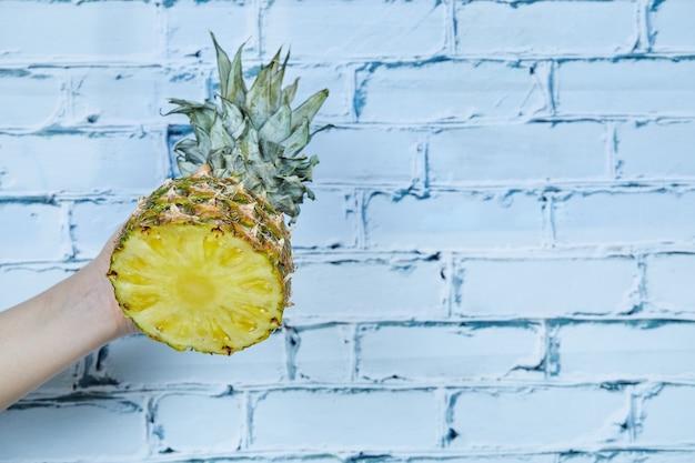 Mão segurando metade do abacaxi em fundo azul