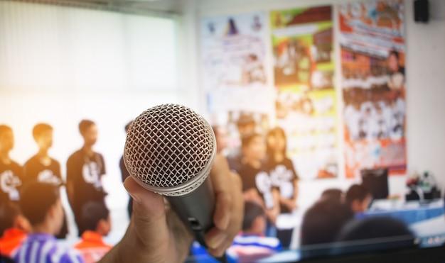 Mão, segurando, microfone, abstratos, borrado, frente, podium, discurso, sala de seminário