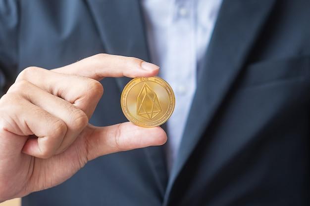 Mão segurando moeda eos de ouro