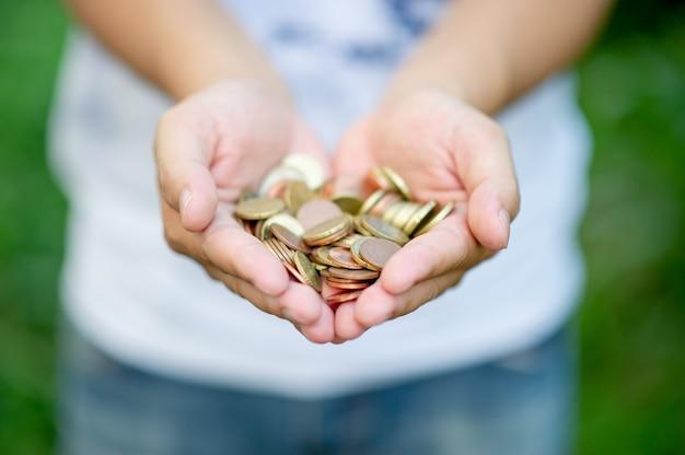 Mão segurando moedas de prata