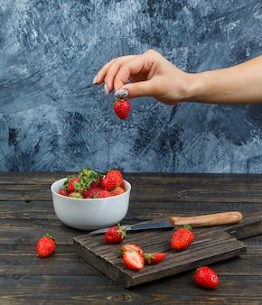 Mão segurando morango sobre frutas