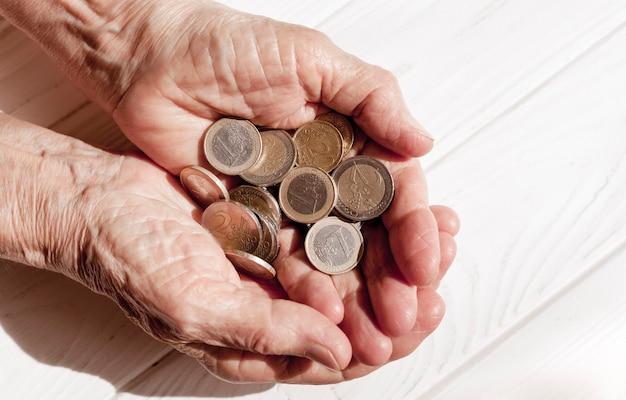 Mão segurando muitas moedas de euro
