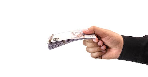 Mão segurando notas de 200 reais, conceito da economia brasileira, inflação, crise financeira ou perda