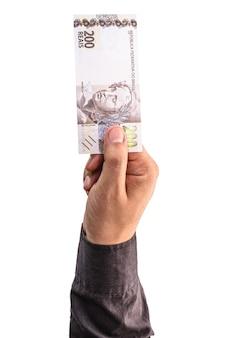Mão segurando notas de 200 reais, dinheiro brasileiro