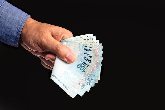 Mão segurando notas de centenas de reais do brasil, ajuda governamental de emergência paga a microempresários