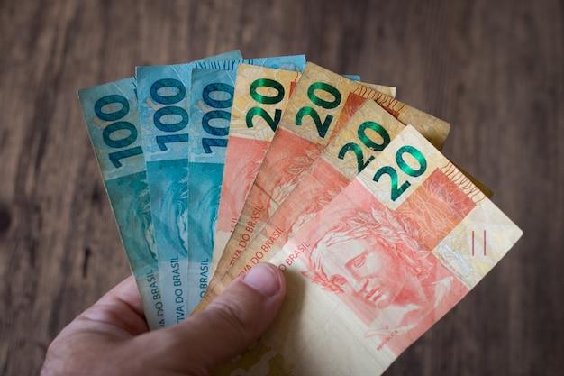 Mão segurando notas de dinheiro brasileiro. conceito de finanças.
