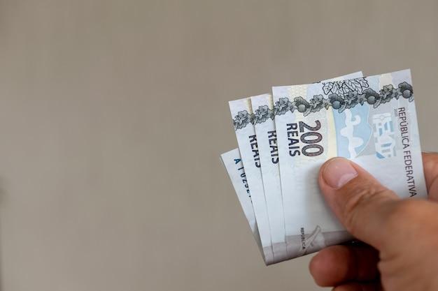 Mão segurando notas de dinheiro do brasil